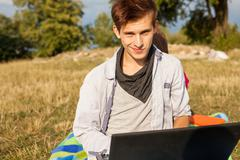 Happy young man in park writing article on his laptop. Stock Photos