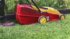 Woman cutting the grass with electric lawn mower Stock Footage