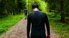 SWEDEN: Camera moving behind a muddy tired male young athlete in jungle Stock Footage