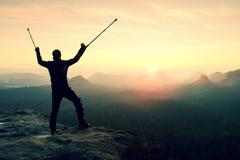 Hiker with  medicine crutch above head achieved mountain peak. - stock photo