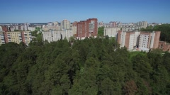 Fly away from the city over the tops of the pine forest in sunny day Stock Footage