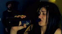 Sad man in dark looking girlfriend getting drunk with wine bottle Stock Footage