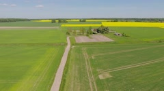 Establishing shot, countryside, flight over small farm by canola field, aerial. - stock footage