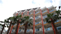 Establishing shot of building with palm trees at front Stock Footage