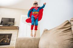 Little boy (2-3) in superman costume jumping on sofa Kuvituskuvat