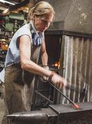 Female blacksmith working in workshop Stock Photos