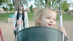 Mom Pushing Little Girl on the Swing Stock Footage