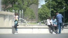 Milan, Italy - Fountain la turta di spus - Teenagers sitting having rest, spring Stock Footage