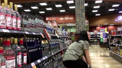 Worker exhibiting wine on the display rack inside BC liquor store - stock footage