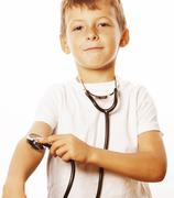 Little cute boy with stethoscope playing like adult profession doctor close up Stock Photos