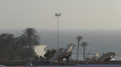 Satellite dishes, palm trees and sea before storm Stock Footage