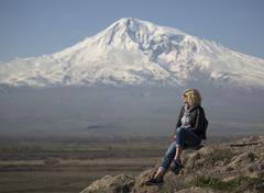 Beautiful blondie woman  is looking into the distance near of Ararat Mount - stock photo