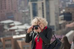 Beautiful blondie woman with curly hair is making photo - stock photo