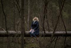 Blondie girl is seating on the trunk  in the  forest and watching to the sky. Stock Photos