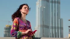 Woman with smartphone and earpieces listens to music Stock Footage