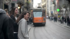Beautiful brunette girls smiling waiting on the tram stop - tram rides Stock Footage