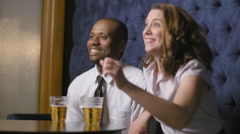 Business people cheering TV sports in lounge bar 4K Stock Footage