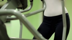 Woman trains in gym. Woman on a orbitrek exercise equipment Stock Footage