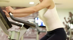 Woman sits on an exercise bike and turns pedals. Woman goes in for sports Stock Footage