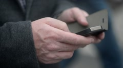 Mobile phone in man's hand chating in the street of Milan - close up Stock Footage