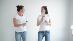 Two girls singing in the paint roller, friends are doing repairs and dancing Stock Footage