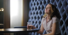 Young business woman waves and beckons friends in lounge bar 4K Stock Footage