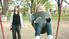Mom Pushing Little Girl on the Swing Wide Stock Footage