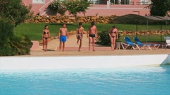 Five young people warm up, make exercises in front swimming pool. Summer sunny Stock Footage