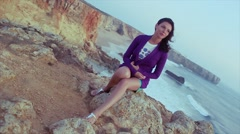 Brunette young girl in purple jacket, shorts sitting on rock at sea. Summer Stock Footage