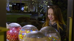 Teen Selects A Gumball, She Pops It In Her Mouth, Laughs At Someone Off-Screen Stock Footage