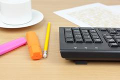 Financial accountants desktop showing a computer keyboard and pens - stock photo