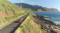 AERIAL: Couple in red convertible car driving along the beautiful coastal road - stock footage