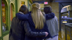 Friends Walk Past Shops, Inside A Mall, Blonde Puts Her Arms Around Them Stock Footage