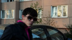Brunette man in sunglasses shaking in camera on street in evening. Black jacket Stock Footage