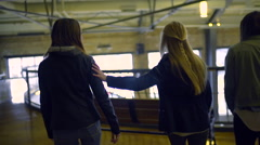 Teens Find A Bench To Sit On Inside, Girl Puts Her Arm Around Friend As They Sit Stock Footage