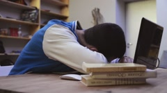 Young boy in jacket wake up after sleeping in front screen of computer. Look - stock footage