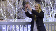 Cute Teen Takes Selfies, With Beautiful Christmas Lights On Trees In Background Stock Footage
