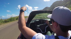 CLOSEUP: Man in luxury red convertible driving along the beach in sunny Hawaii Stock Footage