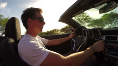 CLOSE UP: Happy man in convertible driving along coastal road, listening music - stock footage