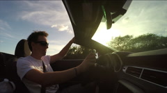 CLOSE UP: Joyful guy driving in luxury cabriolet, listening music and dancing Stock Footage