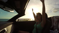 SLOW MOTION: Happy woman on summer vacation riding in convertible at sunset - stock footage