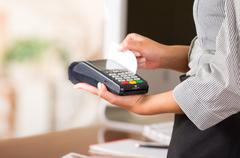 Credit card machine for fast payments, woman hands holding and swiping a white Stock Photos