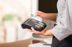 Close up of credit card machine, a woman hand swaping a gray card Stock Photos