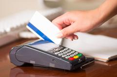 Credit card machine close up, white card with blue band swiping in the machine Stock Photos