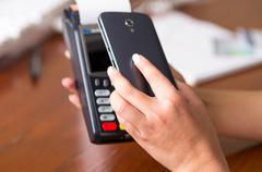 Close up of black mobile phone and credit card machine, code scan to pay the - stock photo