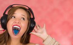 Woman screaming loud with hands holding her headphones, blue tongue and withe - stock photo
