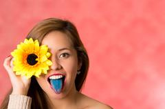 Woman holding a sunflower with one hand cover her eye, blue tongue sticking out Stock Photos