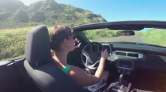 SLOW MOTION: Happy young woman driving cabriolet car on sunny vacation in Hawaii - stock footage