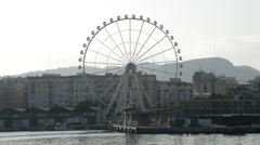 Ferris wheel spinning with buildings of a city at sunset in Malaga, Spain Stock Footage