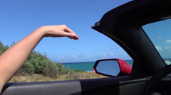 SLOW MOTION CLOSE UP: Driving in convertible car, playing with wind in summer - stock footage